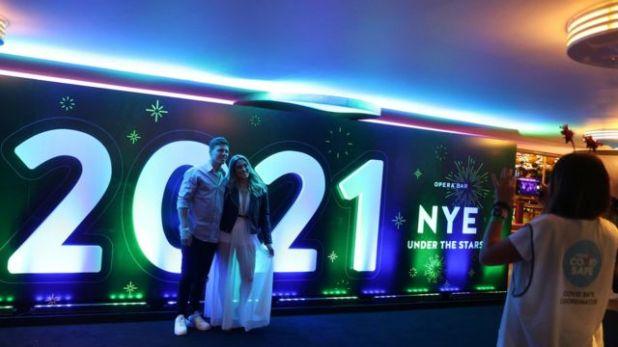 رجل وامرأة يسجلان تاريخ العام الجديد في سيدني في صورة.
