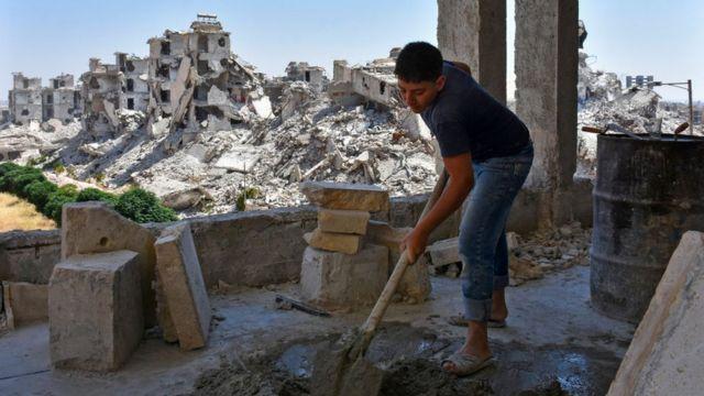 Un joven trabaja en la reconstrucción de casas en Alepo.