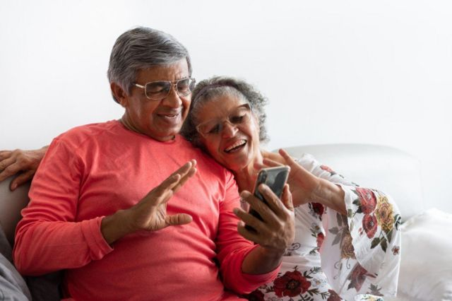 Adultos mayores ven un celular