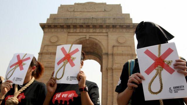 Activistas de Amnistía Internacional con capuchas negras y una soga alrededor del cuello mientras protestan contra la pena de muerte en Nueva Delhi en octubre de 2008.