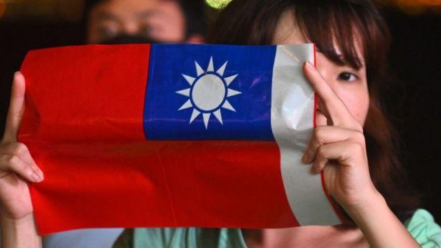 Una mujer sostiene una bandera taiwanesa