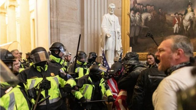 Police face off against pro-Trump rioters beside Abraham Lincoln statue inside of the Capitol