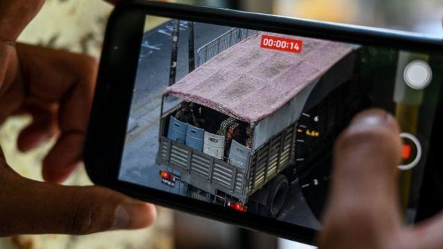 군부가 시위대를 진압하고 있는 가운데 한 시민이 양곤 거리를 이동하는 군부 트럭을 휴대폰으로 촬영하고 있다