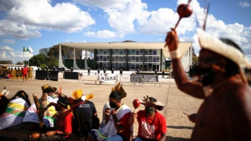 Indigenous people in front of the Supreme Court building for a day, one of them lifting an object