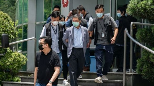Chief Operations Officer Chow Tat Kuen (C) is escorted by police from the headquarters of the Apple Daily newspaper
