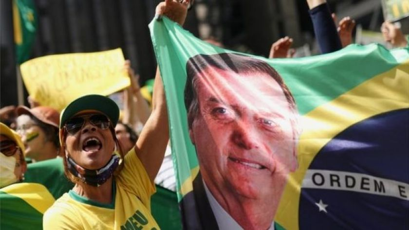 Bolsonaro supporter with the Brazilian flag with the president's face stamped