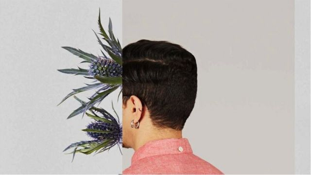 Back of man's head with flowers growing out of the front of his face