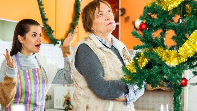 Una mujer y su madre discutiendo en la cocina frente a un árbol de Navidad