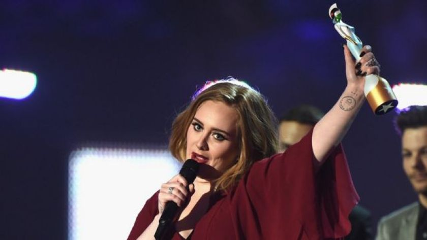 In a ceremony, Adele holds a microphone in one hand and a trophy in the other