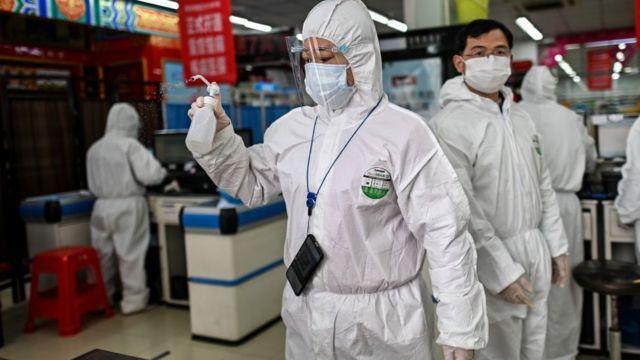 Una mujer vestida con un equipo de protección personal desinfecta una farmacia en Wuhan, en marzo de 2020.