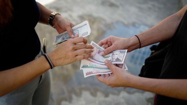 Personas intercambiando billetes de pesos cubanos.