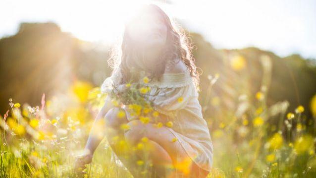 Mulher sob o sol em campo de flores