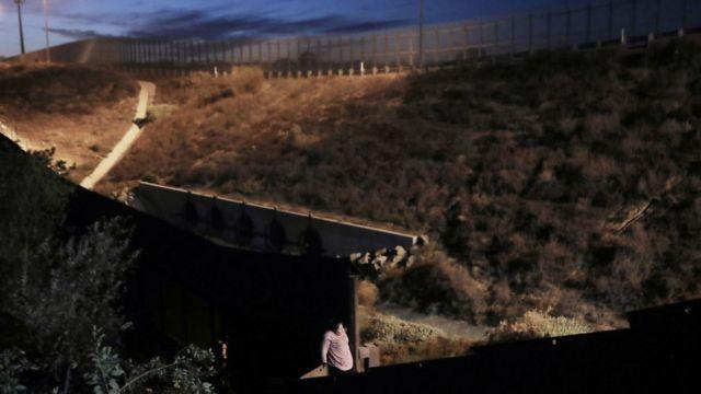 Una mujer cruza el muro fronterizo entre México y Estados Unidos en diciembre de 2018.