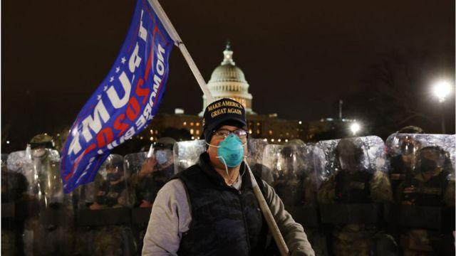 Un hombre con una bandera de Trump manifestándose frente al Capitolio.