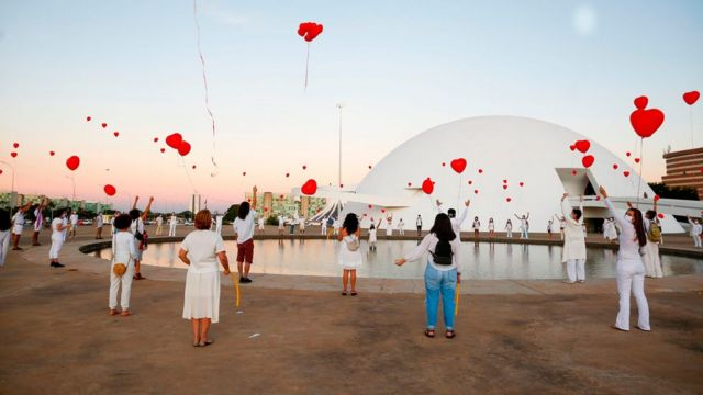 Pessoas de máscara soltando balões vermelhos