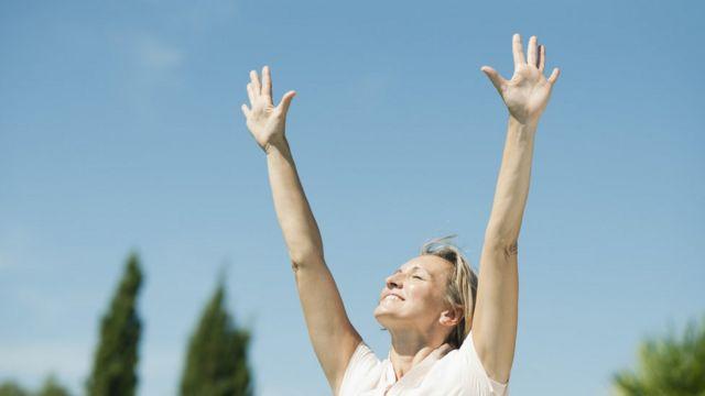 mujer respirando con los brazos en alto