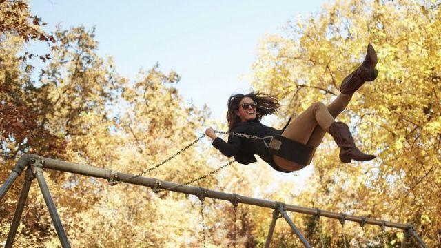 Uma mulher em um balanço no outono