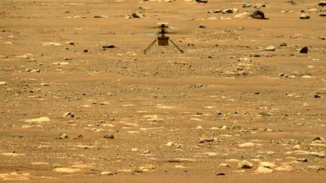 An Ingenuity helicopter flies over the Martian terrain