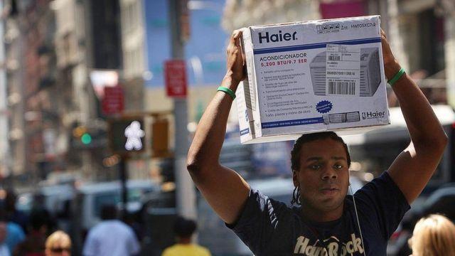 Un hombre carga sobre su cabeza una unidad de aire acondicionado en una calle en Nueva York