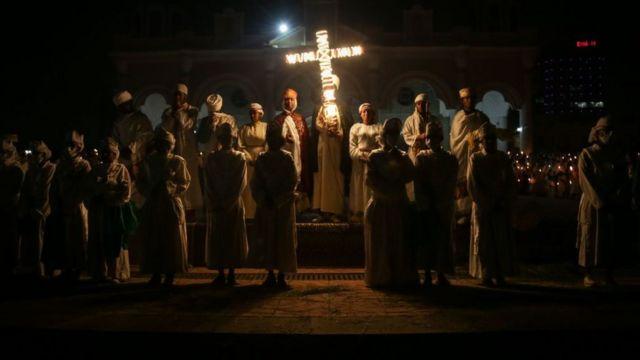 Prayer with illuminated cross