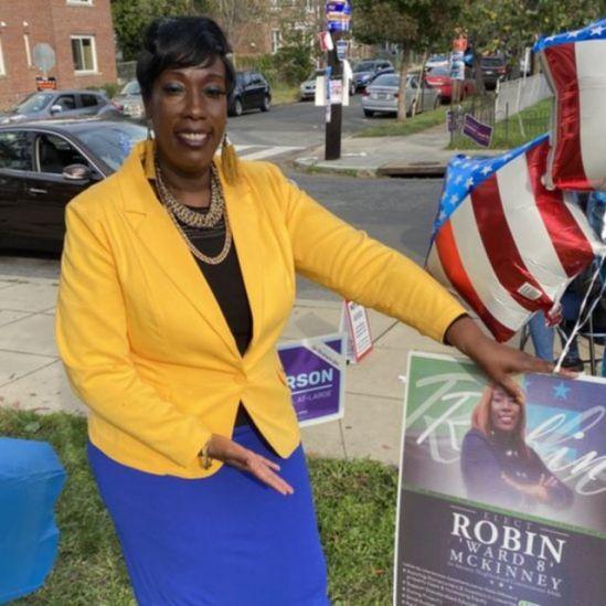 Robin McKinney na rua, sorrindo em meio a bexigas estampadas com bandeira dos EUA
