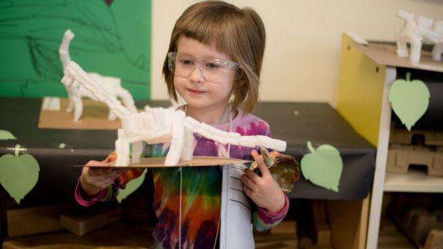 Menina brincando com um dinossauro