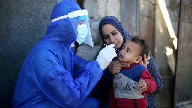 A Palestinian medical worker conducts a coronavirus test for a child