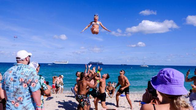 Un grupo de jóvenes lanza por los aires a una chica en Miami Beach