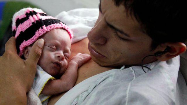 Pai segurando filho recém-nascido