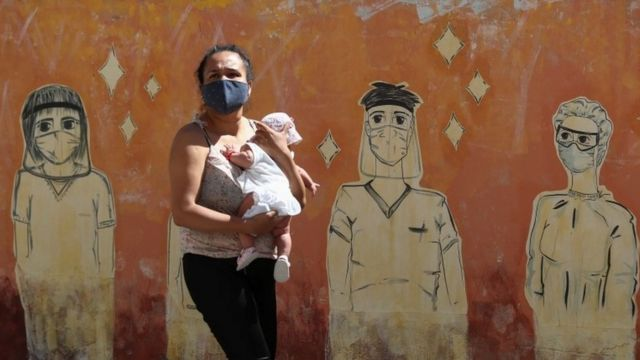 Una mujer con un bebé junto a un mural en Argentina