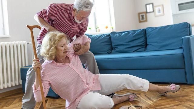 Homem ajudando uma mulher que caiu a se levantar