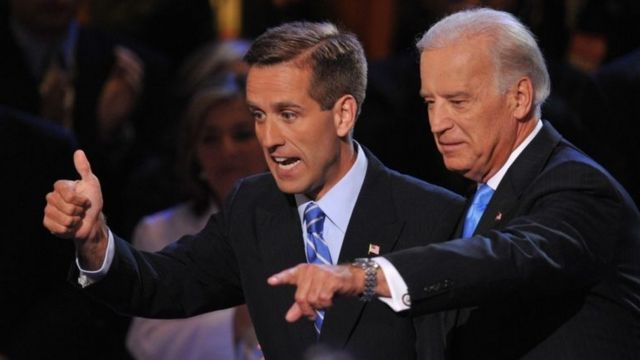 Joe Biden and Beau Biden wave from a stage.