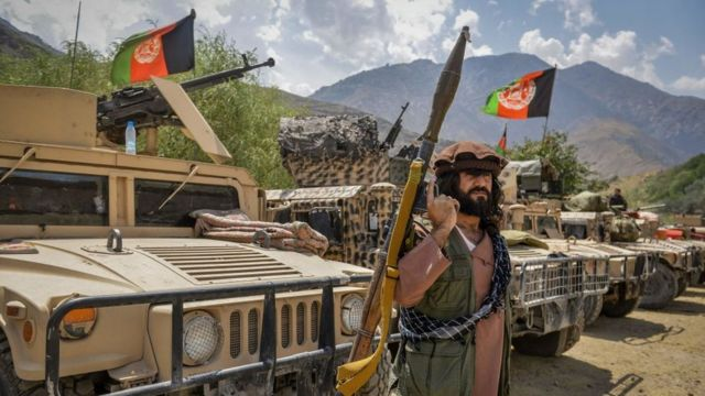 Armed Afghans beside military vehicles in the Parakh area, Bazarak, Panjshir province, on August 19, 2021