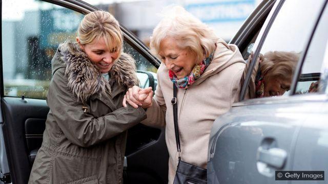 Mulher ajudando idosa a sair do carro