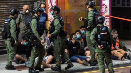 Jovens manifestantes detidos sentados no chão cercados por policiais em Hong Kong