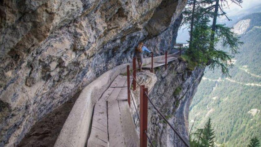 Hiker on the Bisse du Rho trail in Switzerland