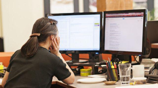 Mulher de cabelo grisalho, sentada e de costas olha para duas telas de computador em escritório