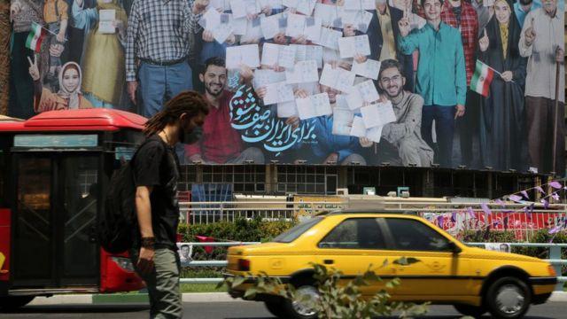 رجل يسير أمام لافتة انتخابية قبل يوم من الانتخابات الرئاسية الثالثة عشرة. طهران، إيران في 17 يونيو/حزيران 2021.