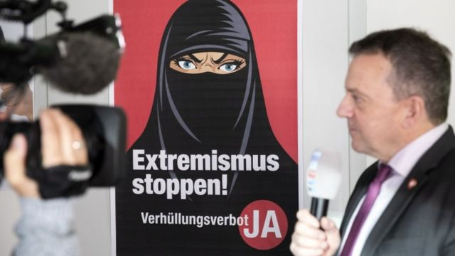 A poster depicting a woman wearing the niqab in Switzerland