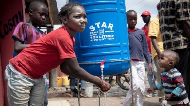 يساعد الأطفال بعضهم البعض في غسل اليدين في محطة غسيل الأيدي في 6 يوليو 2020 في نيروبي ، كينيا