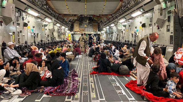 지난 19일 카불 공항의 미국 군수송기에서 출발을 기다리는 아프간 가족들