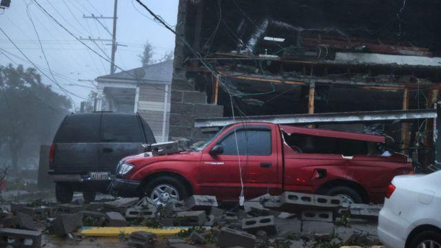 Edificio y vehículos dañados por el paso del huracán Ida.