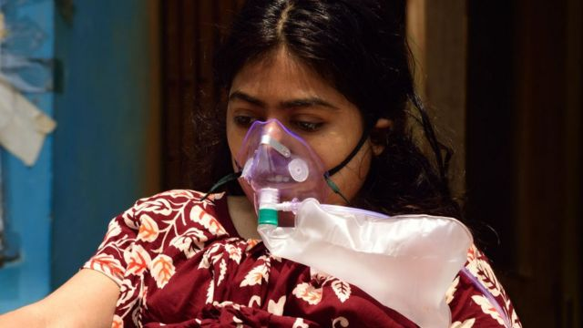 A patient wears a mask while waiting to be admitted to a hospital.