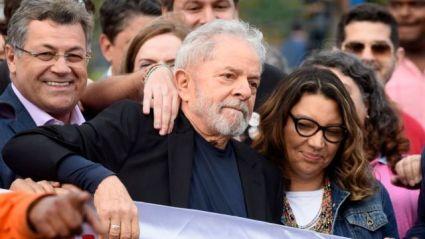 Lula prestes a entrar no carro, com uma multidão em volta e ao lado da namorada Rosangela da Silva