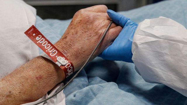 Profissional de saúde segura a mão de paciente com covid-19 no hospital