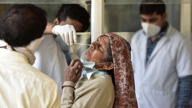 أحد العاملين في القطاع الصحي يجري مسحة لامرأة مسنة - 23 مارس/آذار 2021