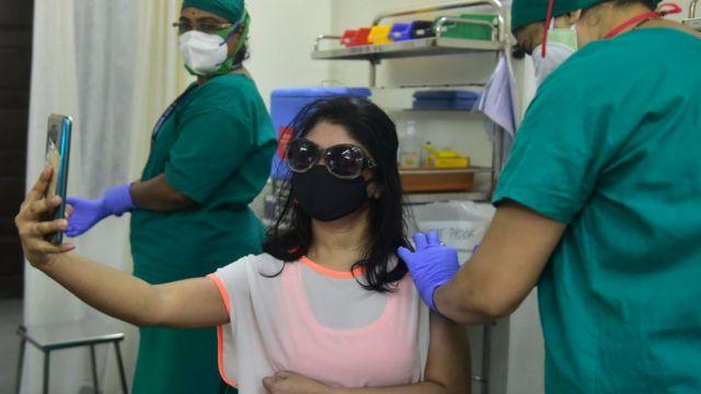 백신 접종 순간을 영상으로 담는 여성