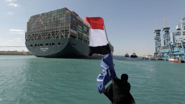 Ships loaded with containers passed by Tuesday in Ismailia, which is located on the west bank of the canal