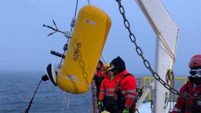 Cientistas extraem uma âncora da água do Ártico com instrumentos que medem o fluxo de calor do interior do oceano para a superfície