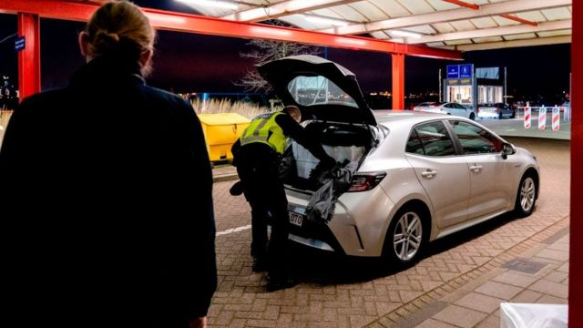 A border agent in Hoek van Holland inspects the trunk of a car coming from the UK